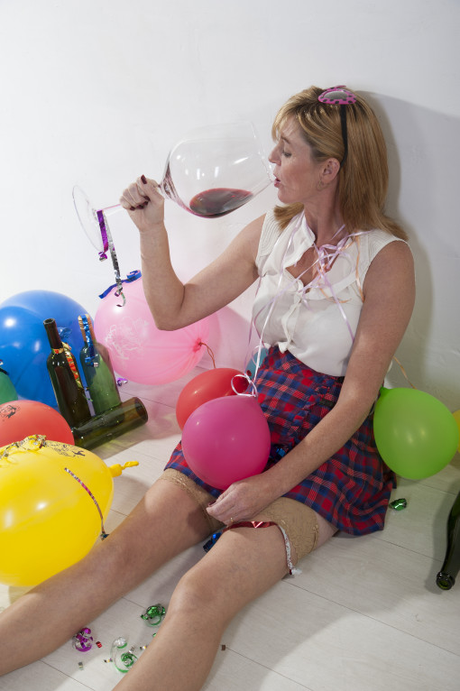 Female party goer drinking alcohol