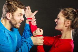Husband fighting with wife. Aggresive man and woman in studio on black. Domestic violence aggression. Bad relationship.