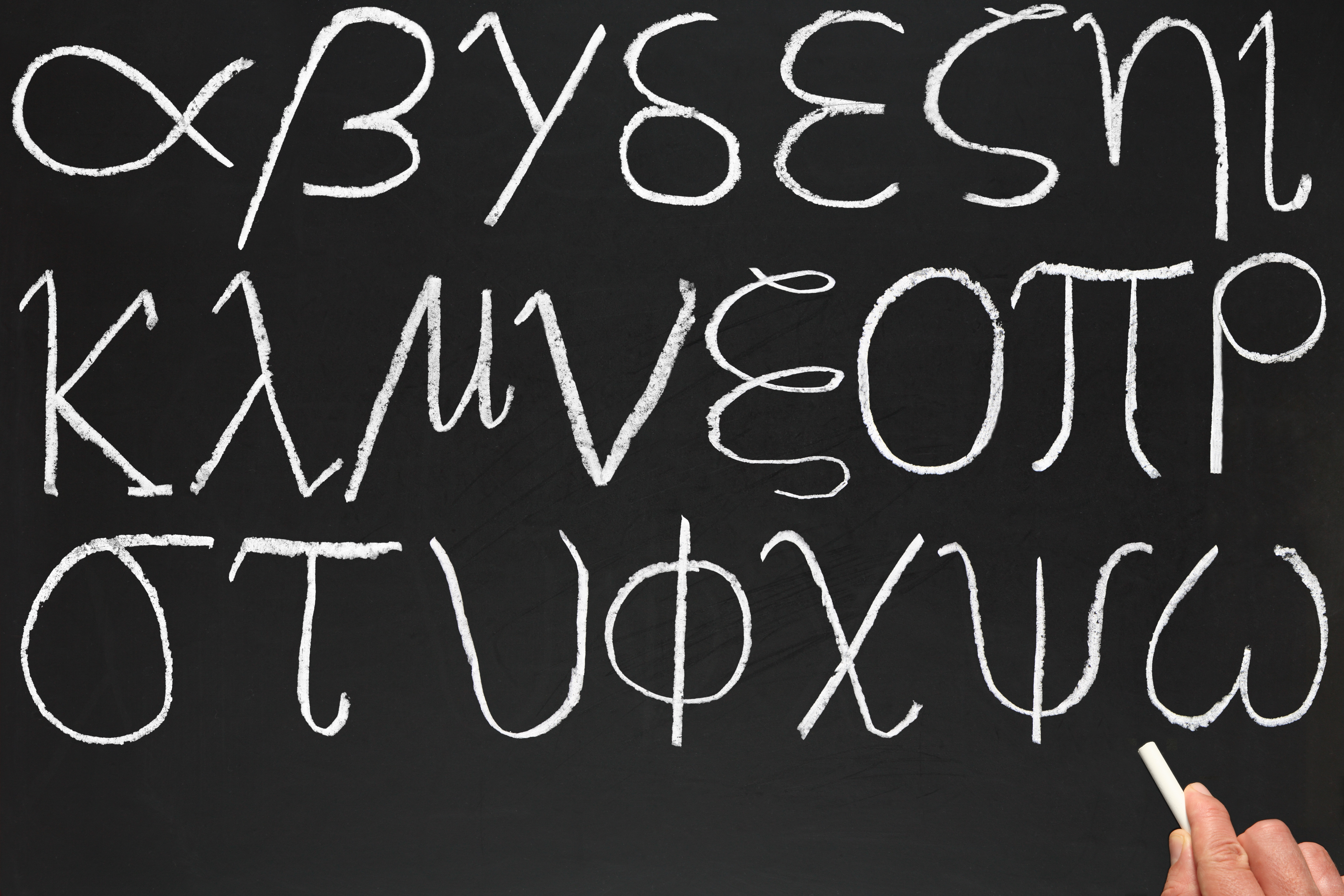 A teacher writing the Greek alphabet on a blackboard.